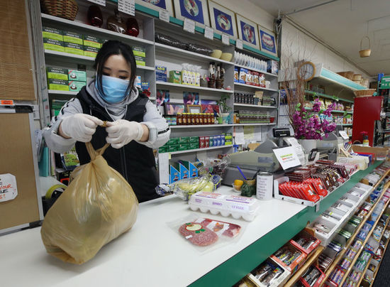 Store Employee Bagging Products in Mask